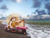 Ребенок сидит в чемодане на море