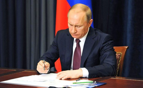 В. Путин подписывает документ